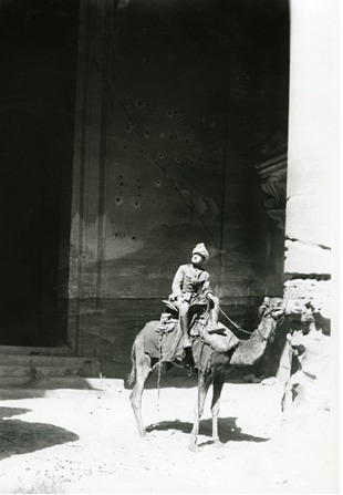Lowell Thomas on camel under column at the Temple of Isis (The Deir), Petra. 1918.