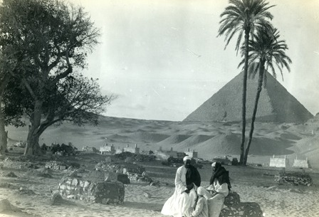 Pyramid, palm trees and men sitting in the foreground. 1918.
