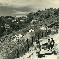 Lowell Thomas being carried along a road in a dandy chair.PNG